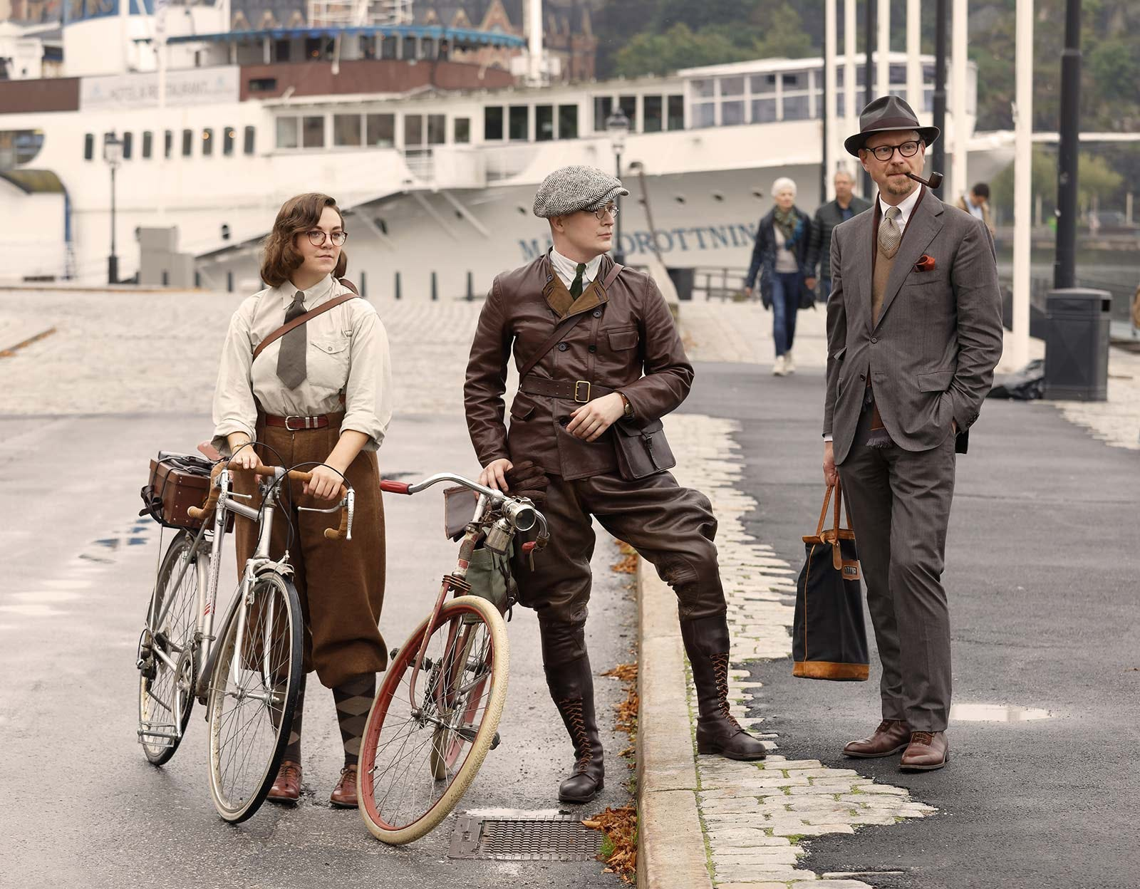 People dressed in vintage tweet outfits with bicycles, posing in front of a passenger ferry.