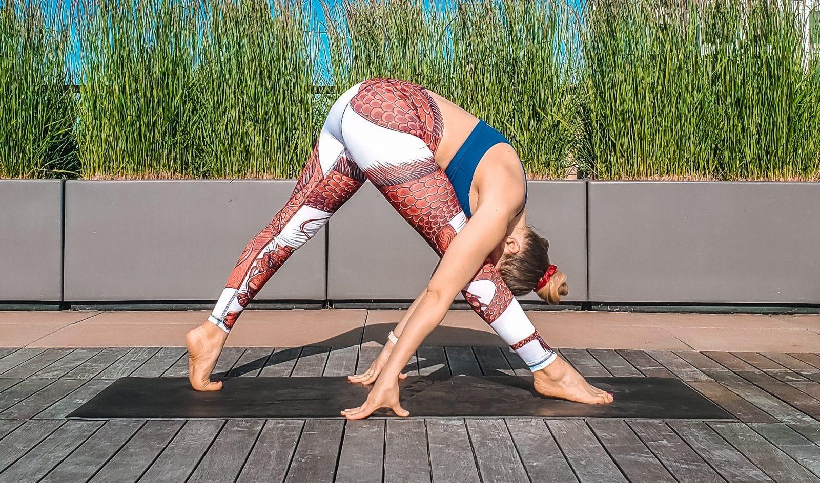 A woman doing a forward fold on a black yoga mat.