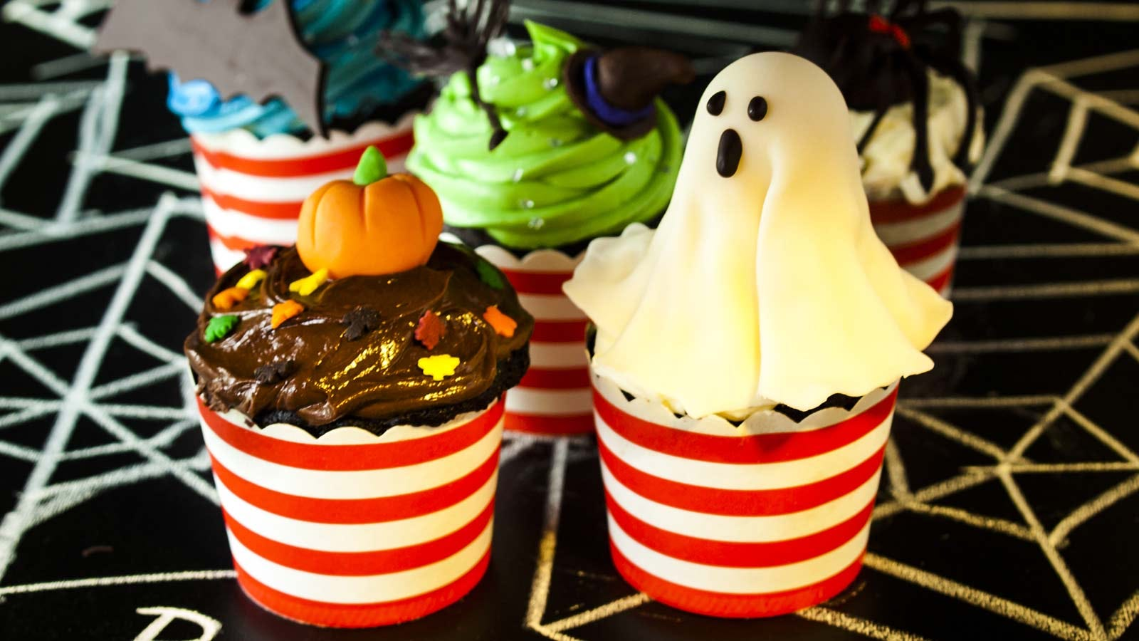 Fancy Halloween cupcakes topped with fondant ghosts, pumpkins, and more.