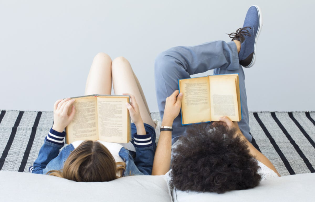 two teenagers reading books by each other