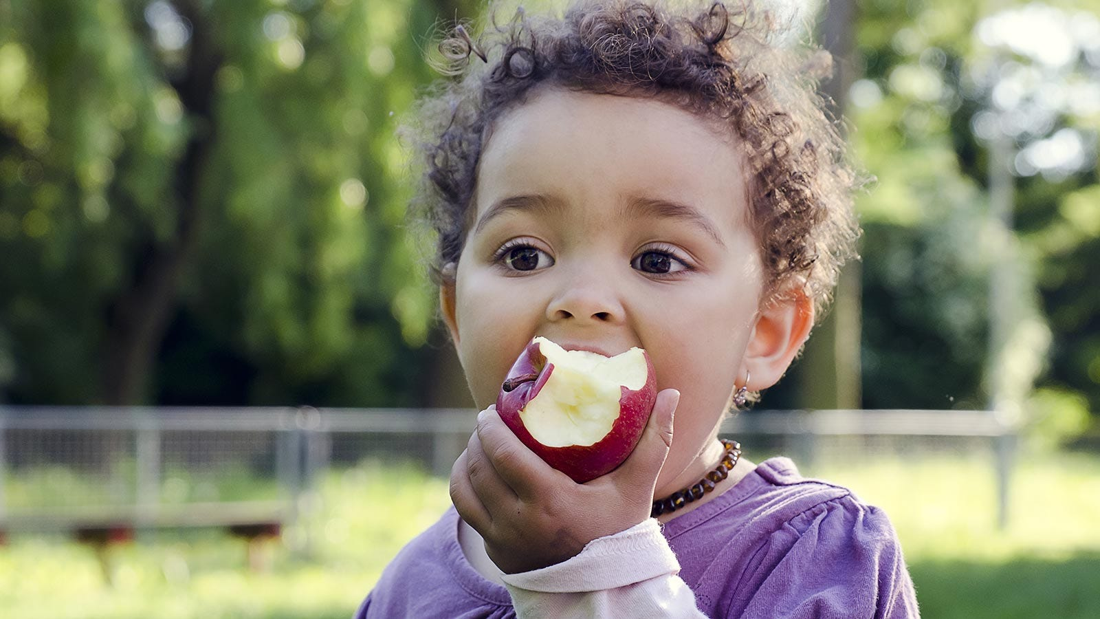 A young girl enjoying an apple as a healthy snack while playing at the park.