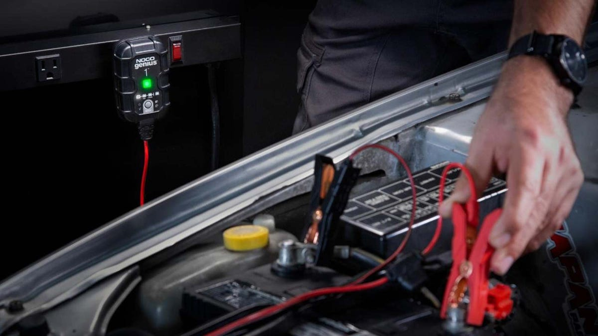 A man hooking charging leads to his car battery.