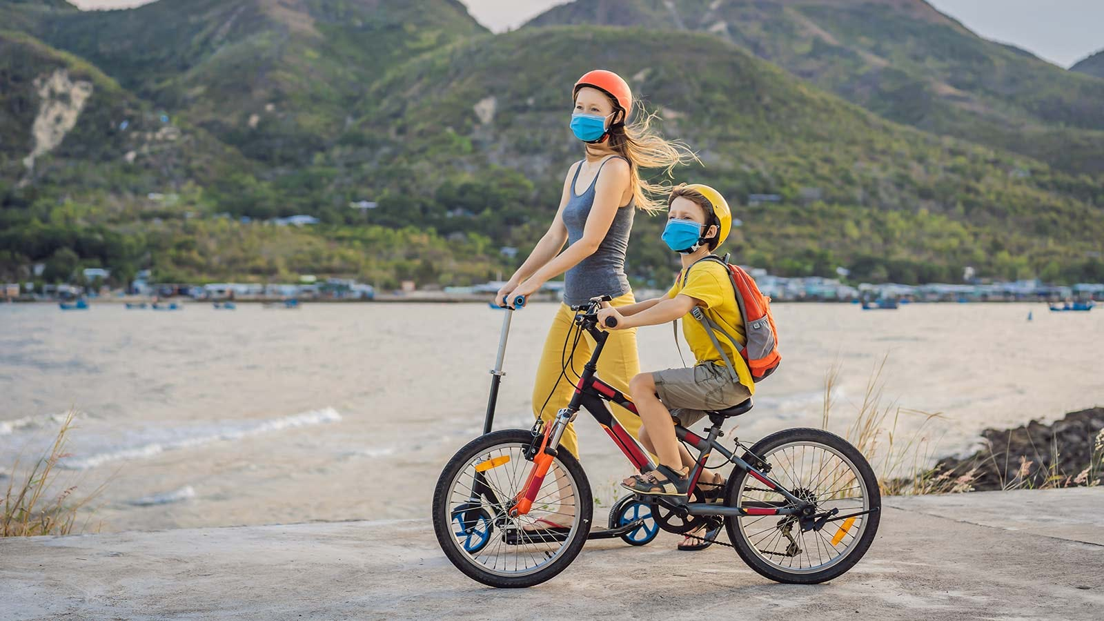 A young girl riding a scooter and a boy riding a bike with masks on.