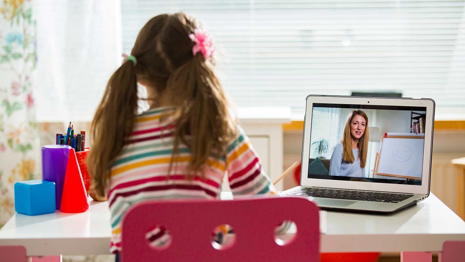 A young girl sitting at a small desk in her bedroom, talking to her teacher by video conference.