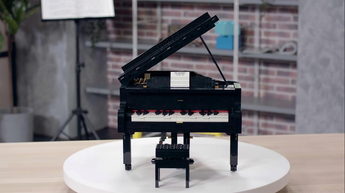 A lego piano sits on a rotating platform