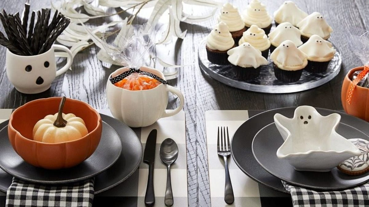 A ghost mug holding black licorice sitting on a table next to a pumpkin bowl, a ghost bowl, and a plate of ghost cookies.