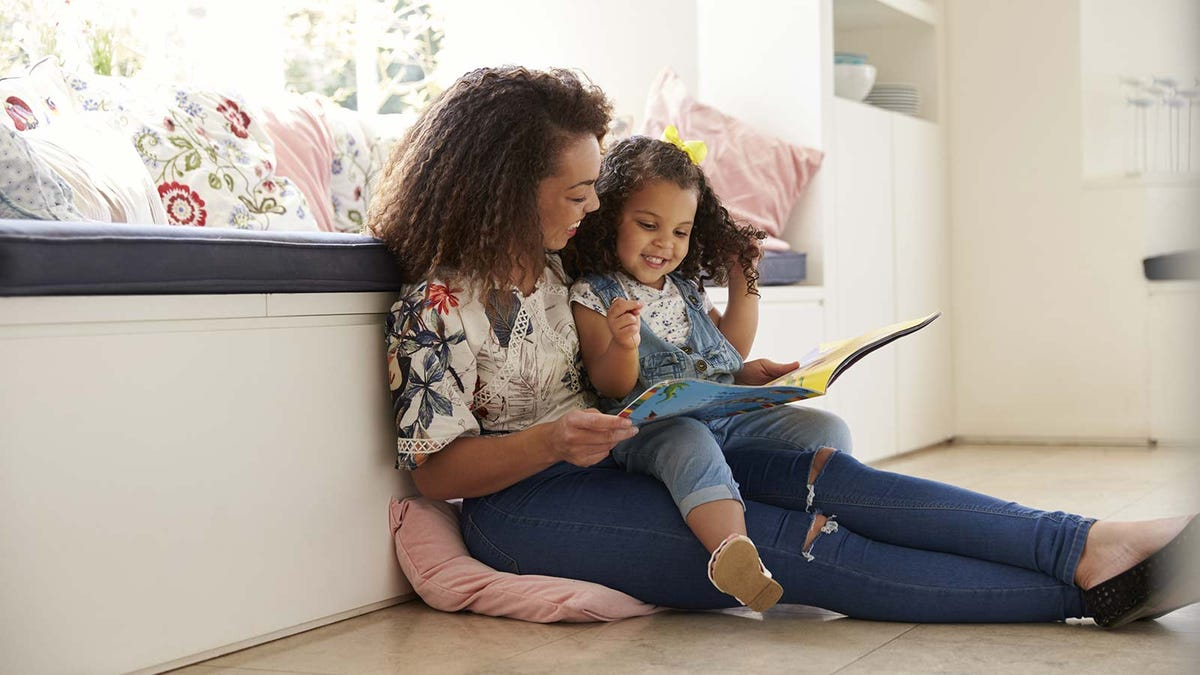 A mother and daughter reading on the floor next to a window seat.