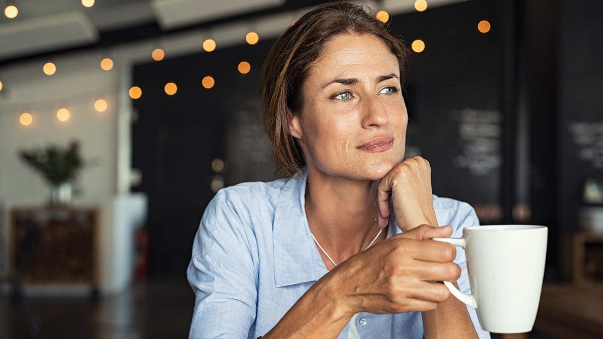 A woman drinking a cup of coffee and taking a moment to reflect on life and relax.