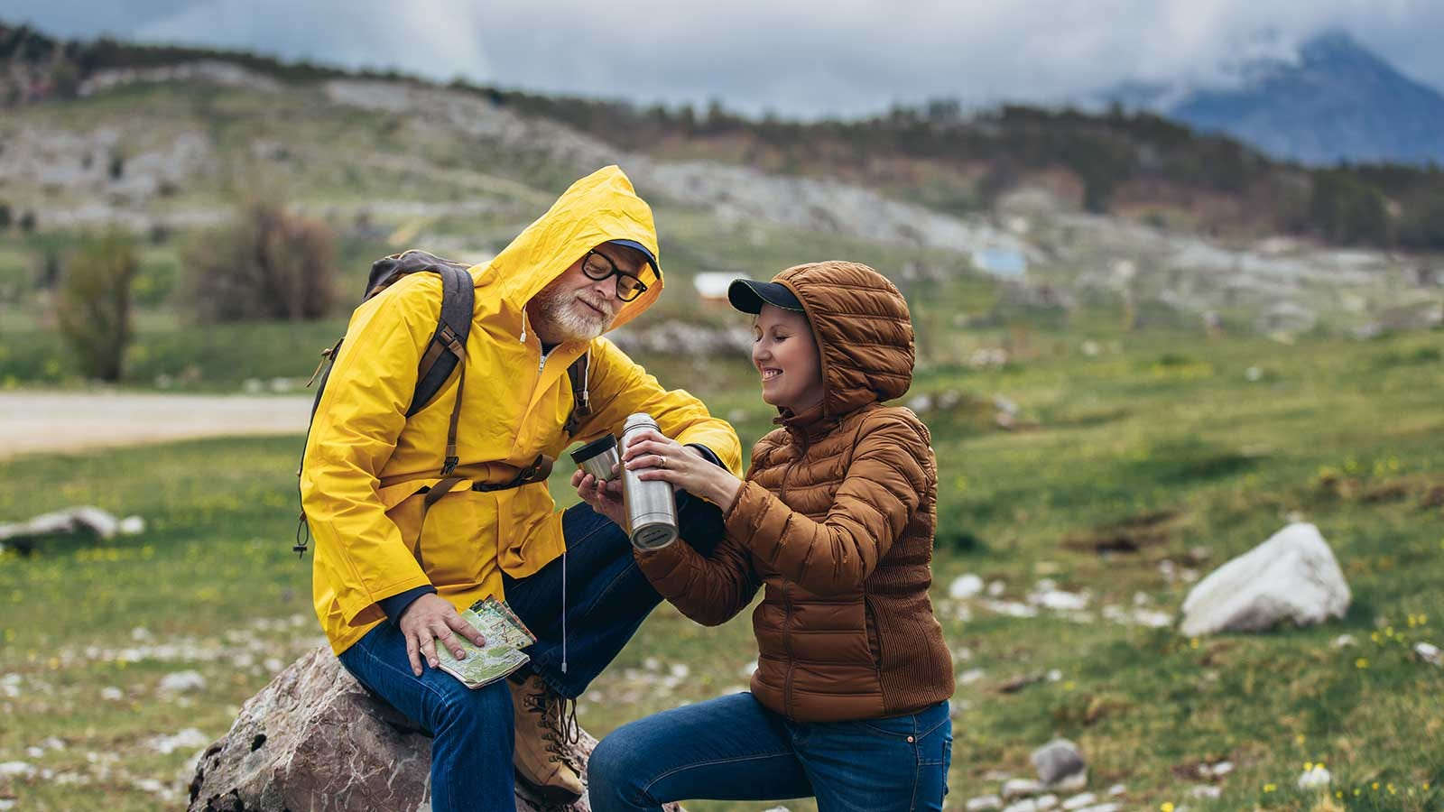 A couple in mid-season cool weather gear, stopping to enjoy some coffee on a hike.