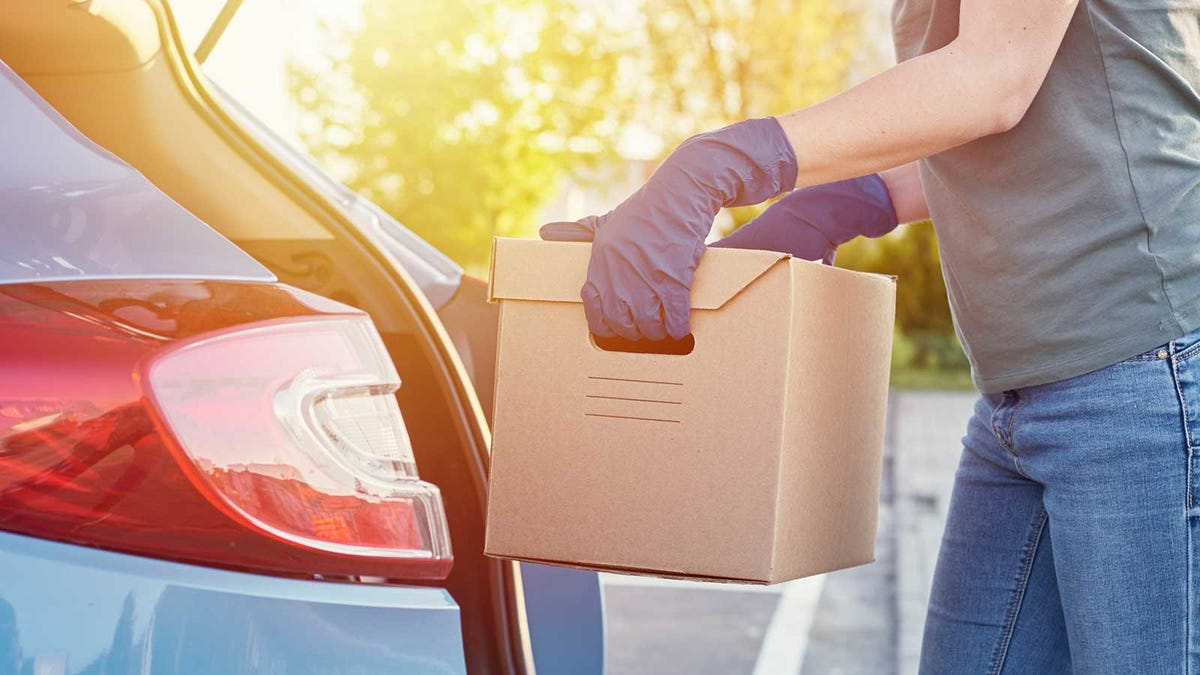 A woman loading moving boxes into her car while wearing gloves.