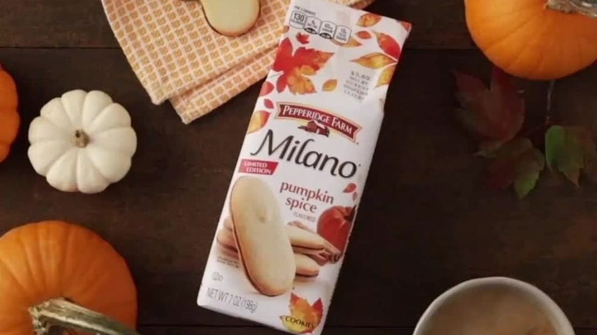 A package of pumpkin spice milano cookies sits in the middle of pumpkins and coffee on a table.