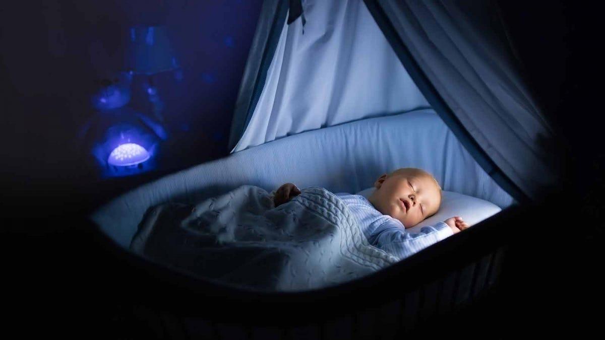 A baby sleeps in a blue basinet.