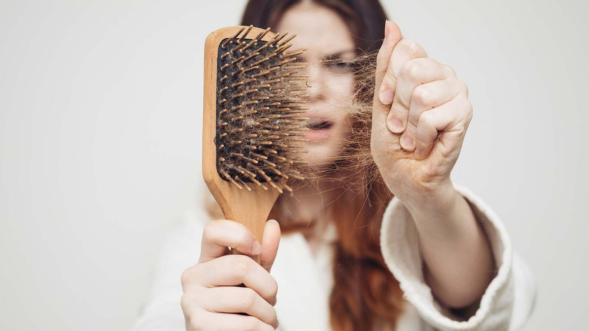 A woman pulling hair out of a hairbrush.