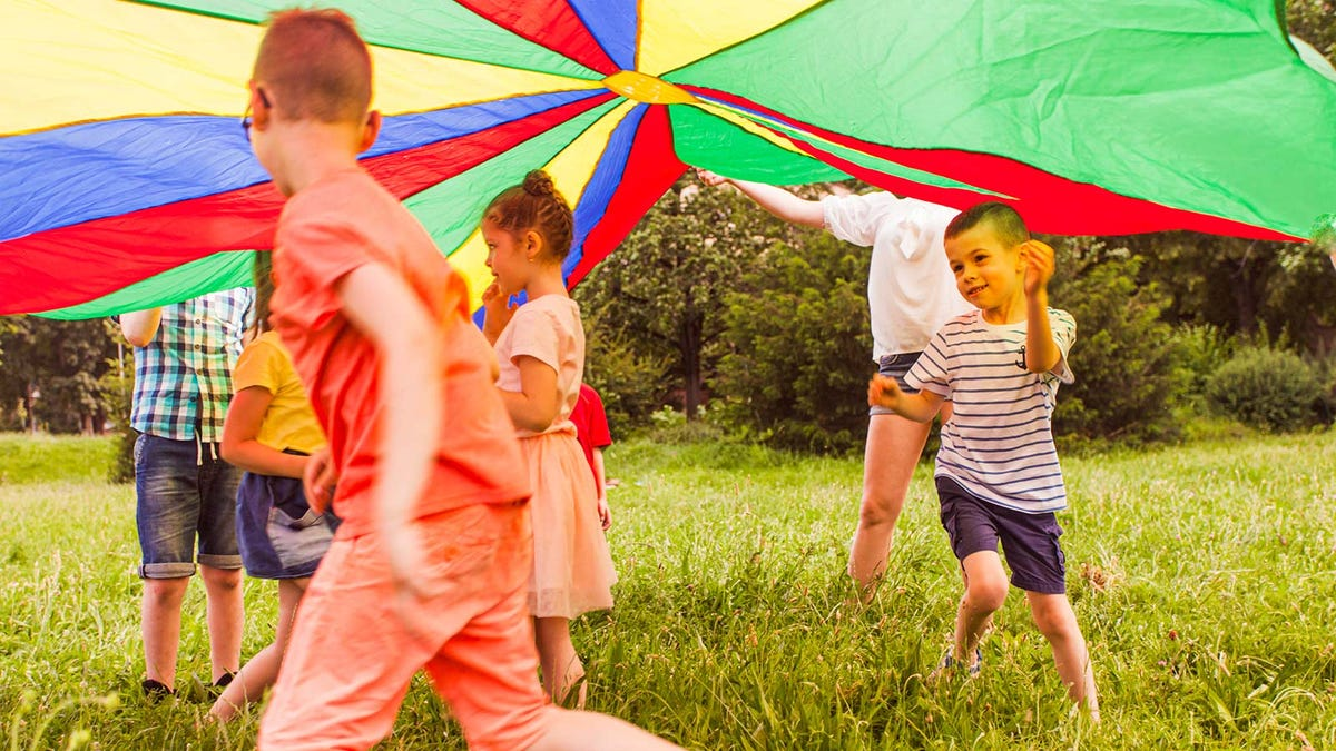 A group of children running and playing under a parachute.