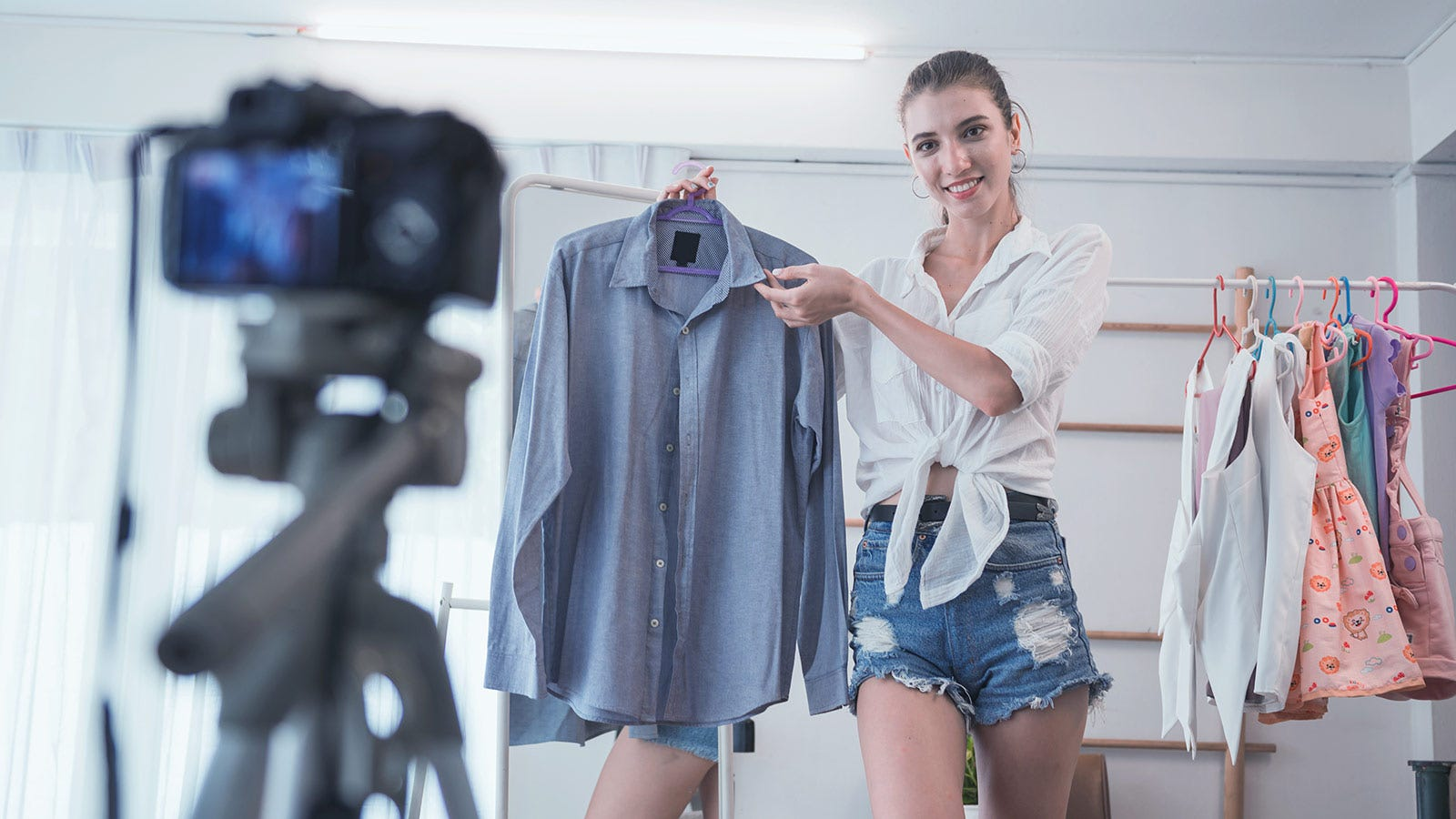 A young girl holding a shirt in front of a camera on a tripod to sell it online..