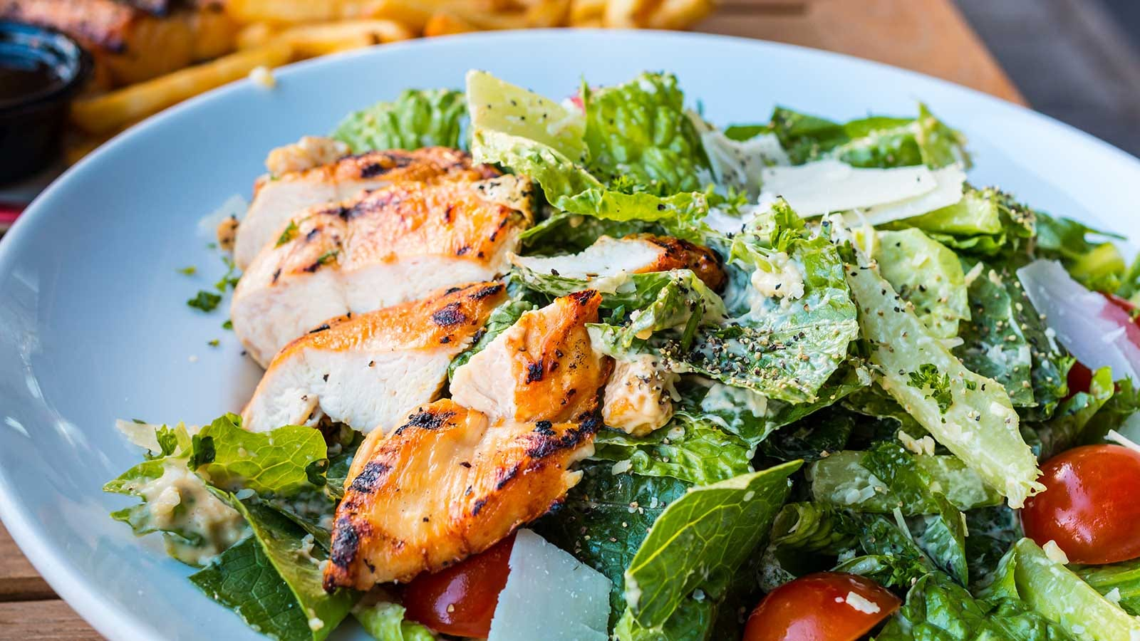 A well tossed salad with the greens evenly coated with fresh salad dressing.