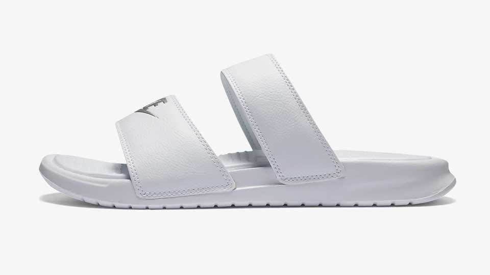 A pair of white Nike Ultra Slide sandals.