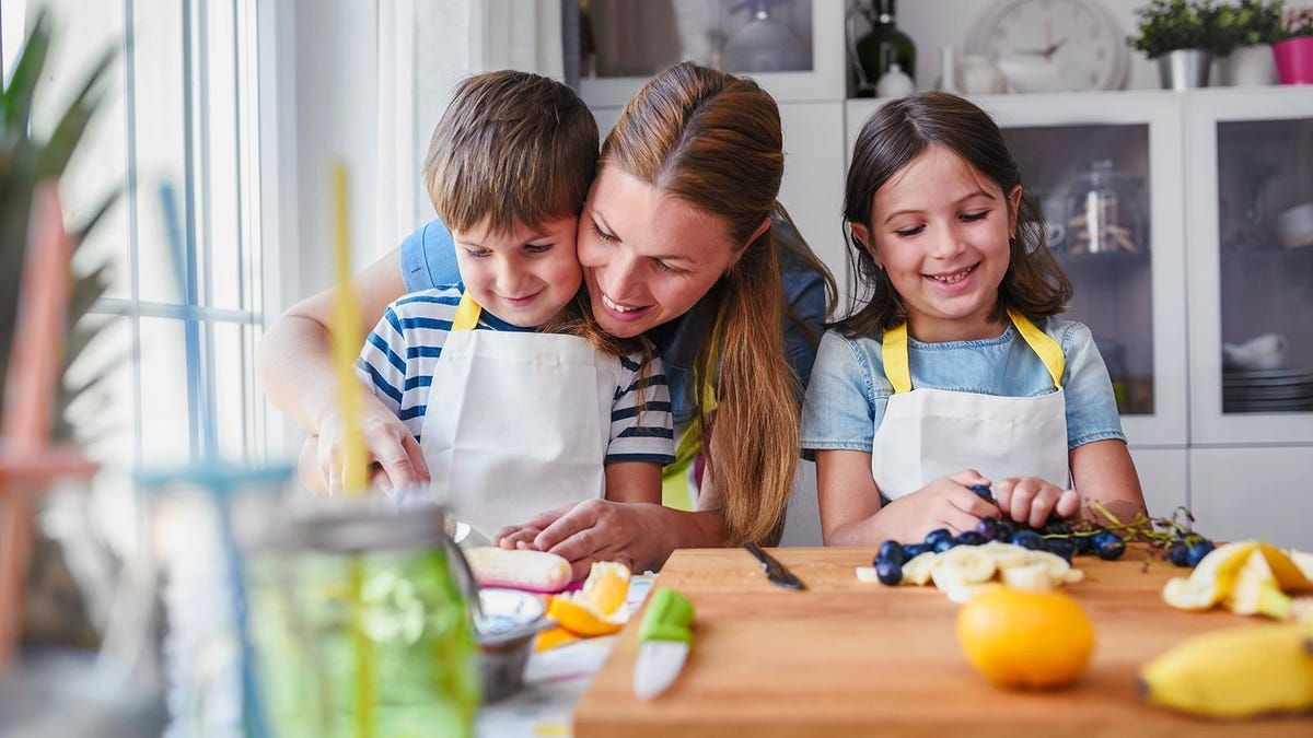 A mother preps some healthy snacks with the help of her children in a sunny kitchen.
