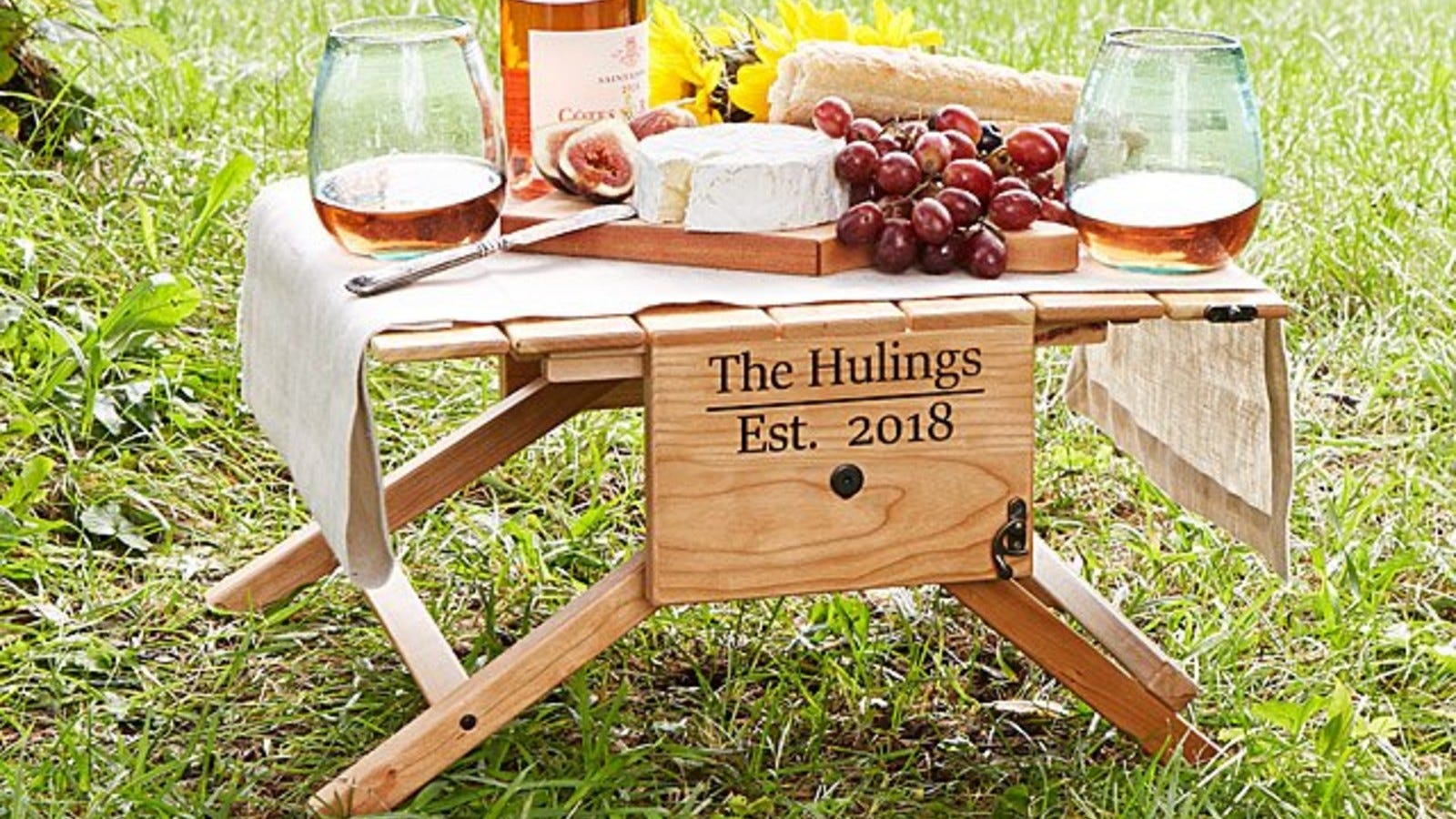 Wine, cheese, and grapes on Uncommon Goods' Personalized Picnic Table.