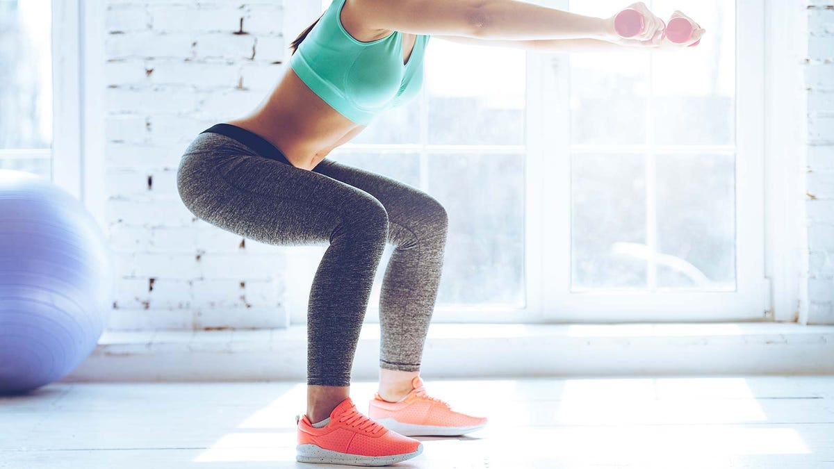 A woman doing squats in a sunny exercise room.