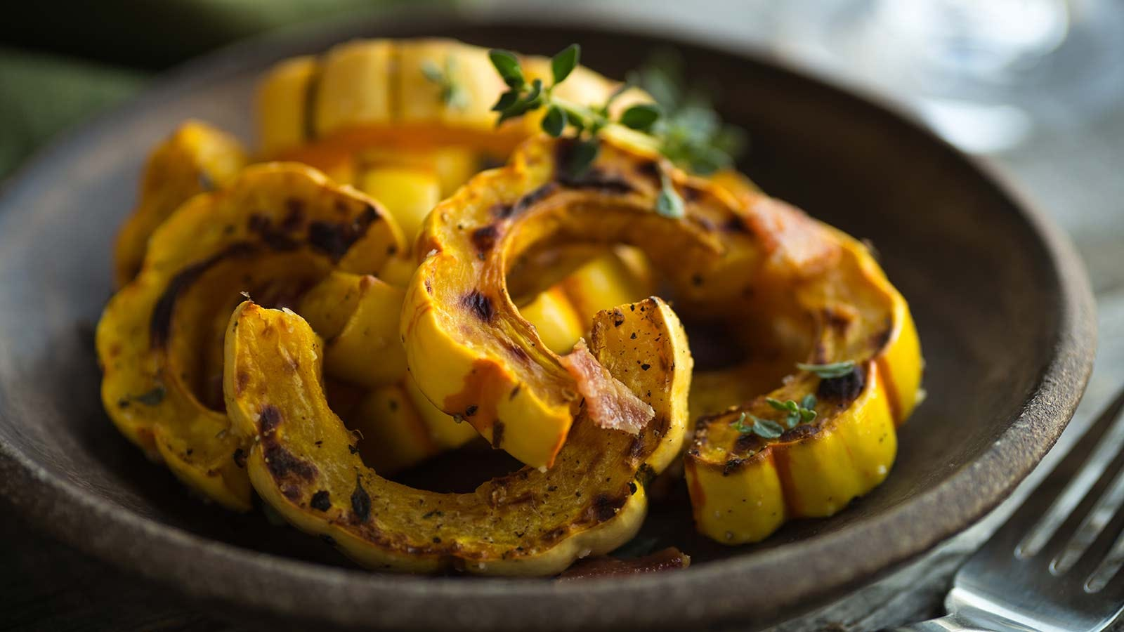 A plate loaded with slices of roasted delicata squash.
