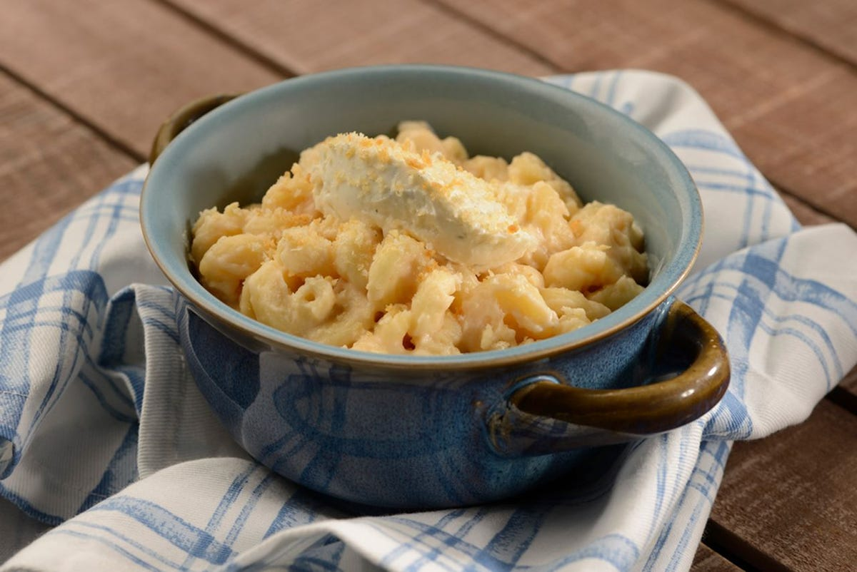 A bowl of macaroni and cheese with boursin on top sit on top of a blue and white towel.