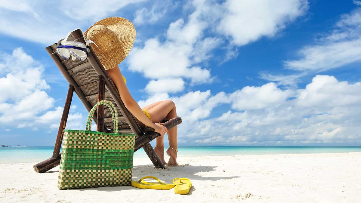 A woman sitting on the beach, her sandals kicked off beside her tote bag.