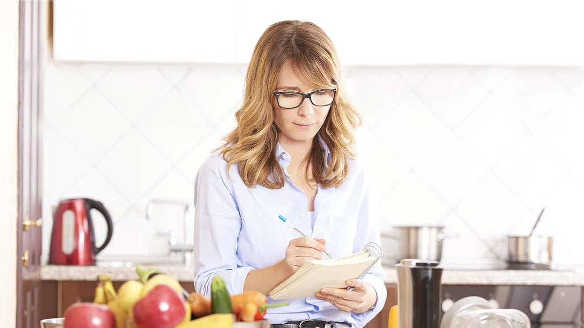 A woman writing in a notebook while standing in a kitchen.
