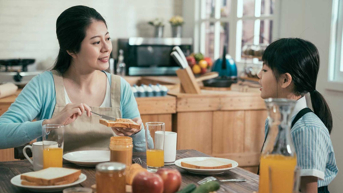 A mother and daughter sharing breakfast in a sunny kitchen, talking about the plan for the day.