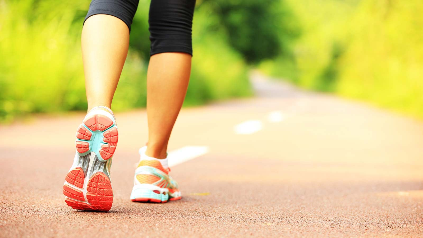 A woman walking a trail in athletic shoes.