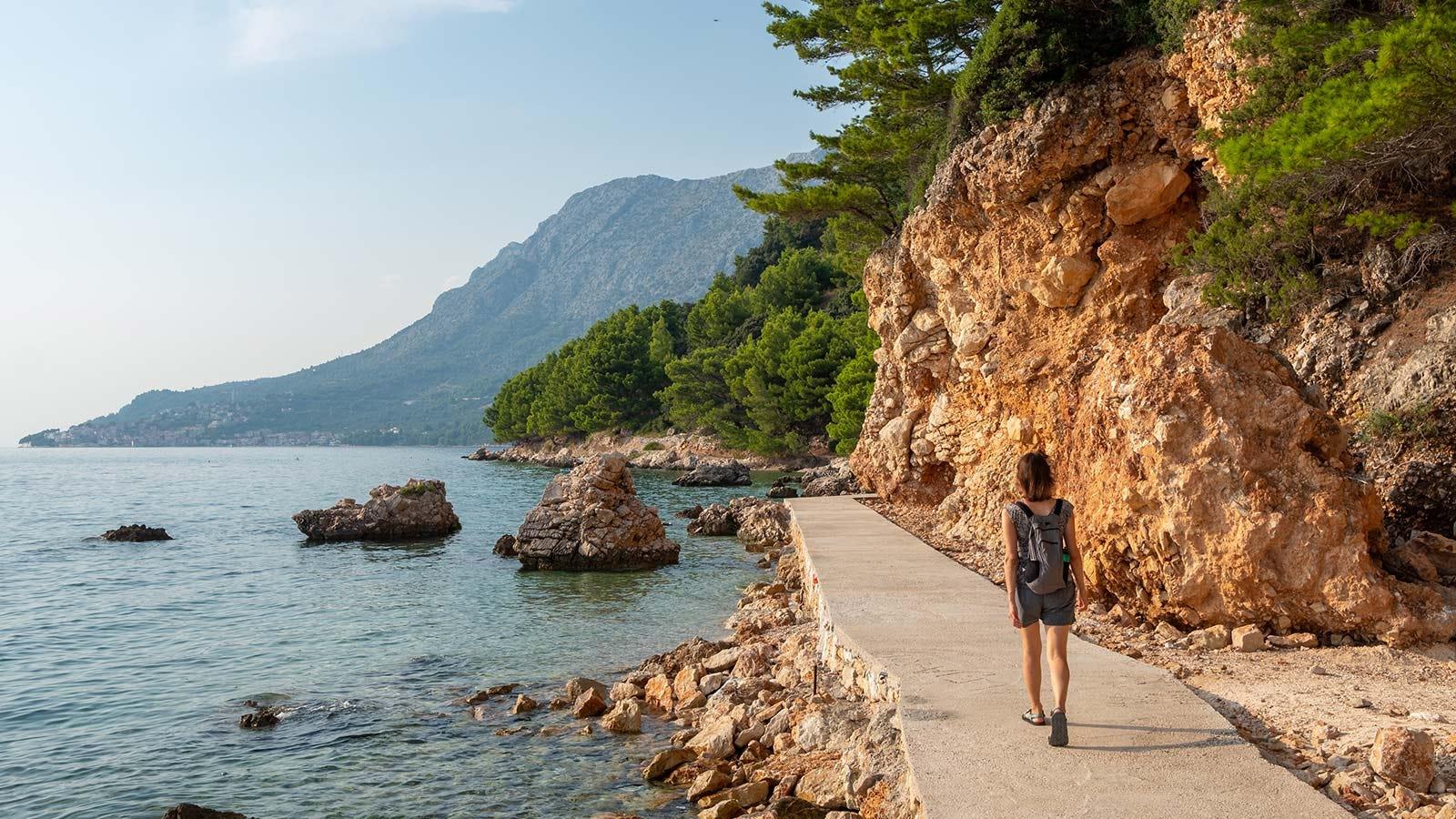 Woman walking along a raised beach path.
