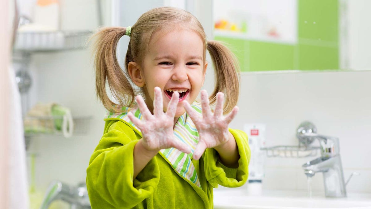 A young girl laughing and smiling while washing her hands.