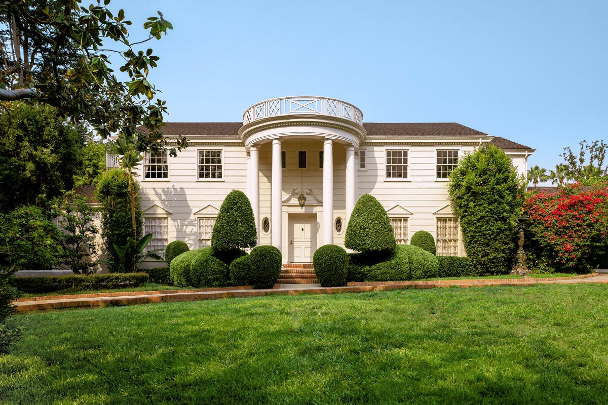 A large mansion with a rounded portico and columns sits behind a green lawn.