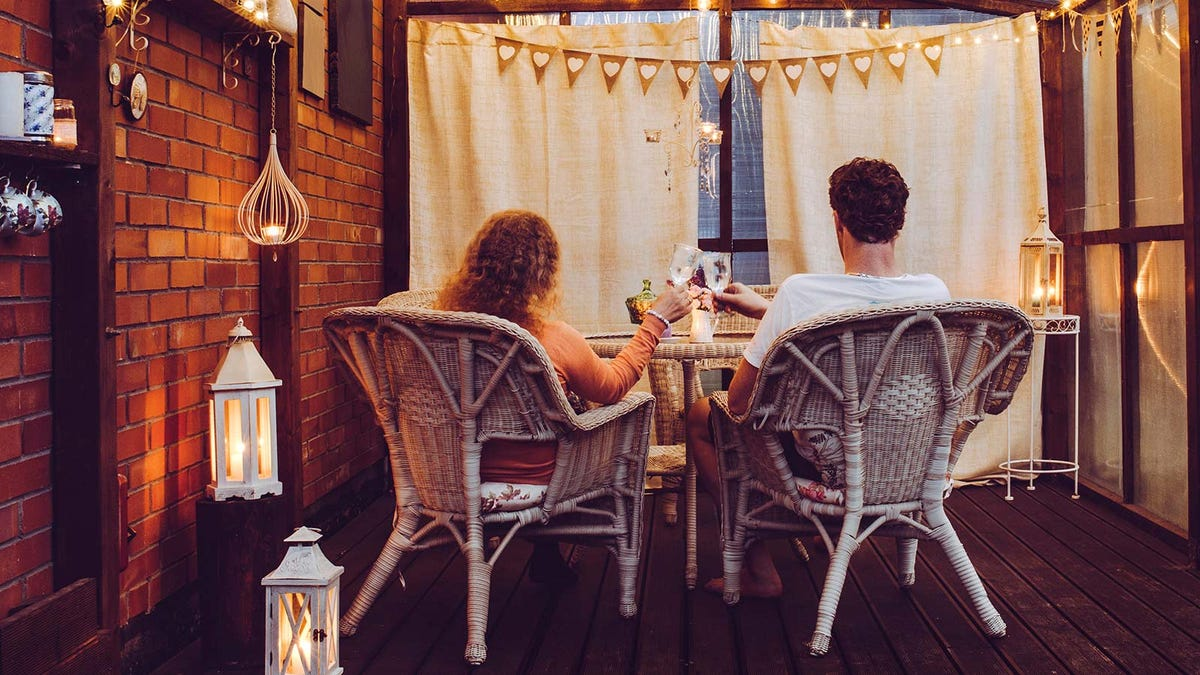 A man and woman toasting glasses of wine, while sitting on a small balcony.