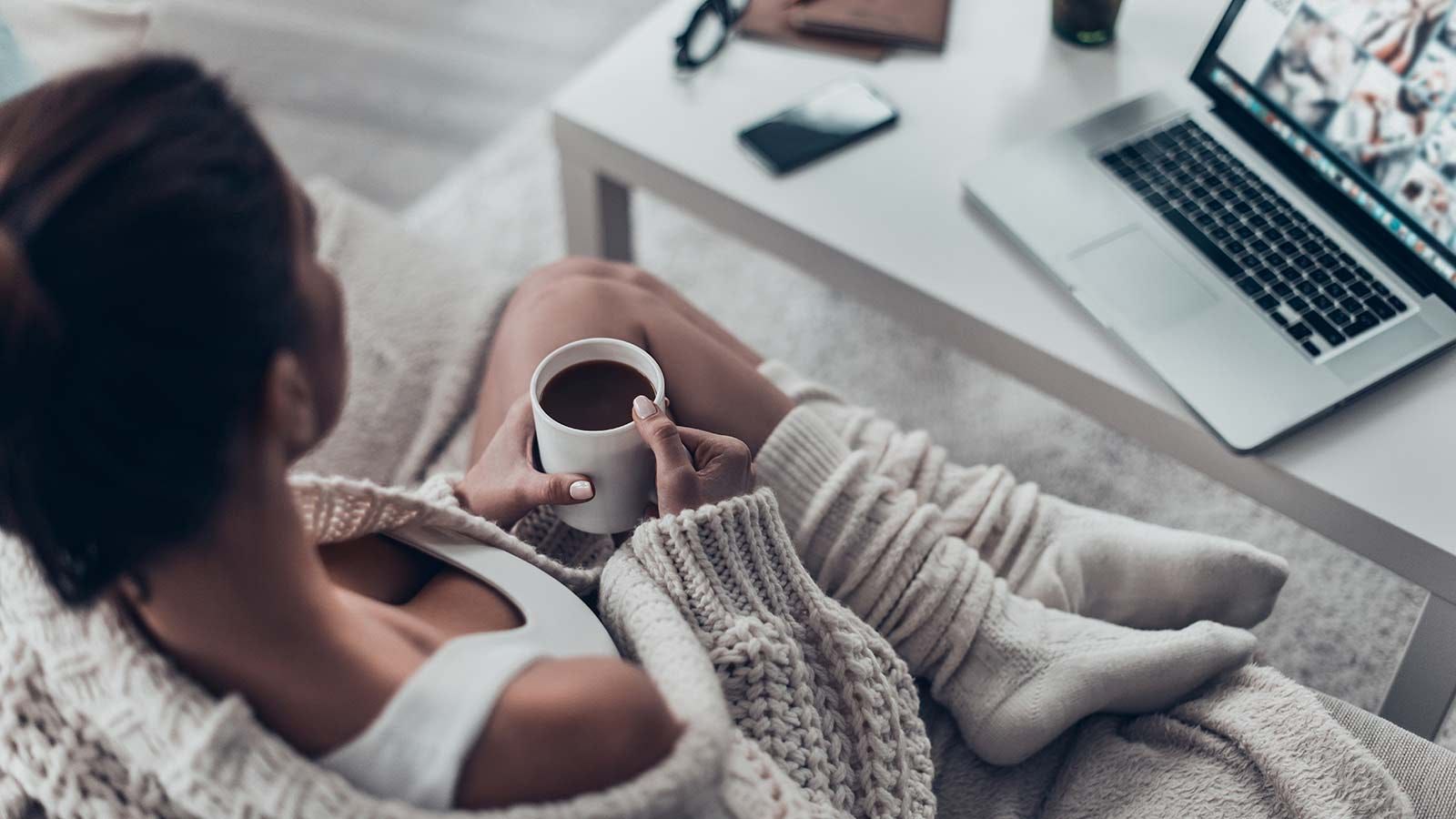 A woman sitting on her couch in a comfy sweater, holding a hot cup of coffee.