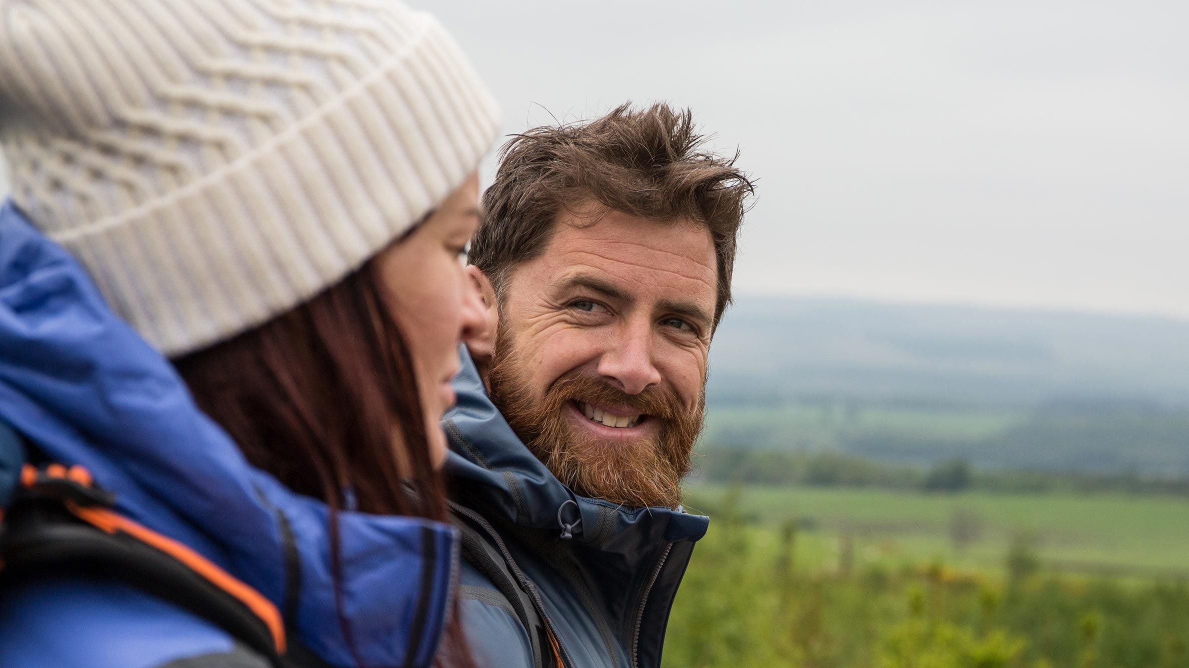 A man and woman wearing Columbia rain jackets.