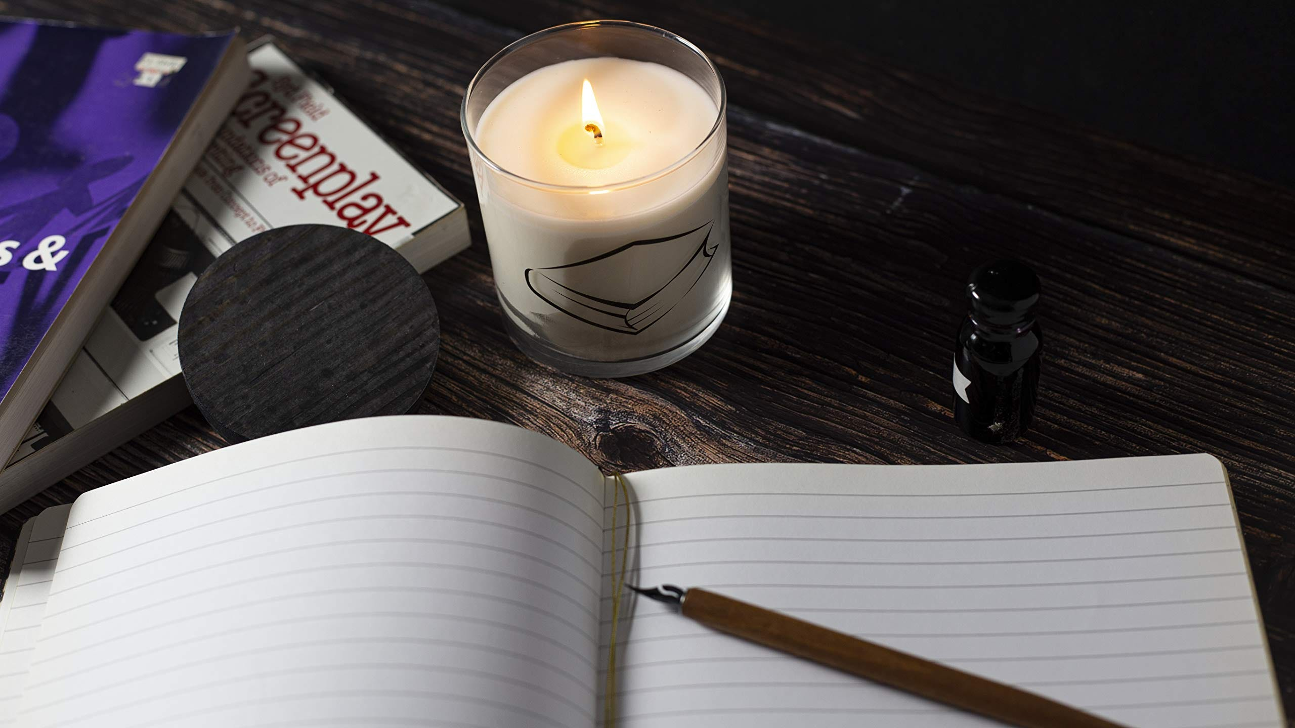 A candle burning on a table beside books, an open notebook, and a bottle of ink.