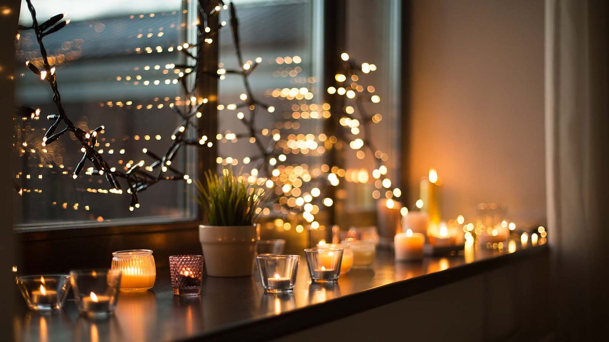 A window sill covered with candles, framed by twinkling Christmas lights.