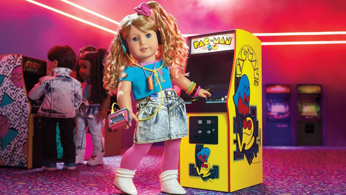 """The """"Courtney"""" 1980s American Girl doll standing next to a tiny arcade game of Pac-Man."""