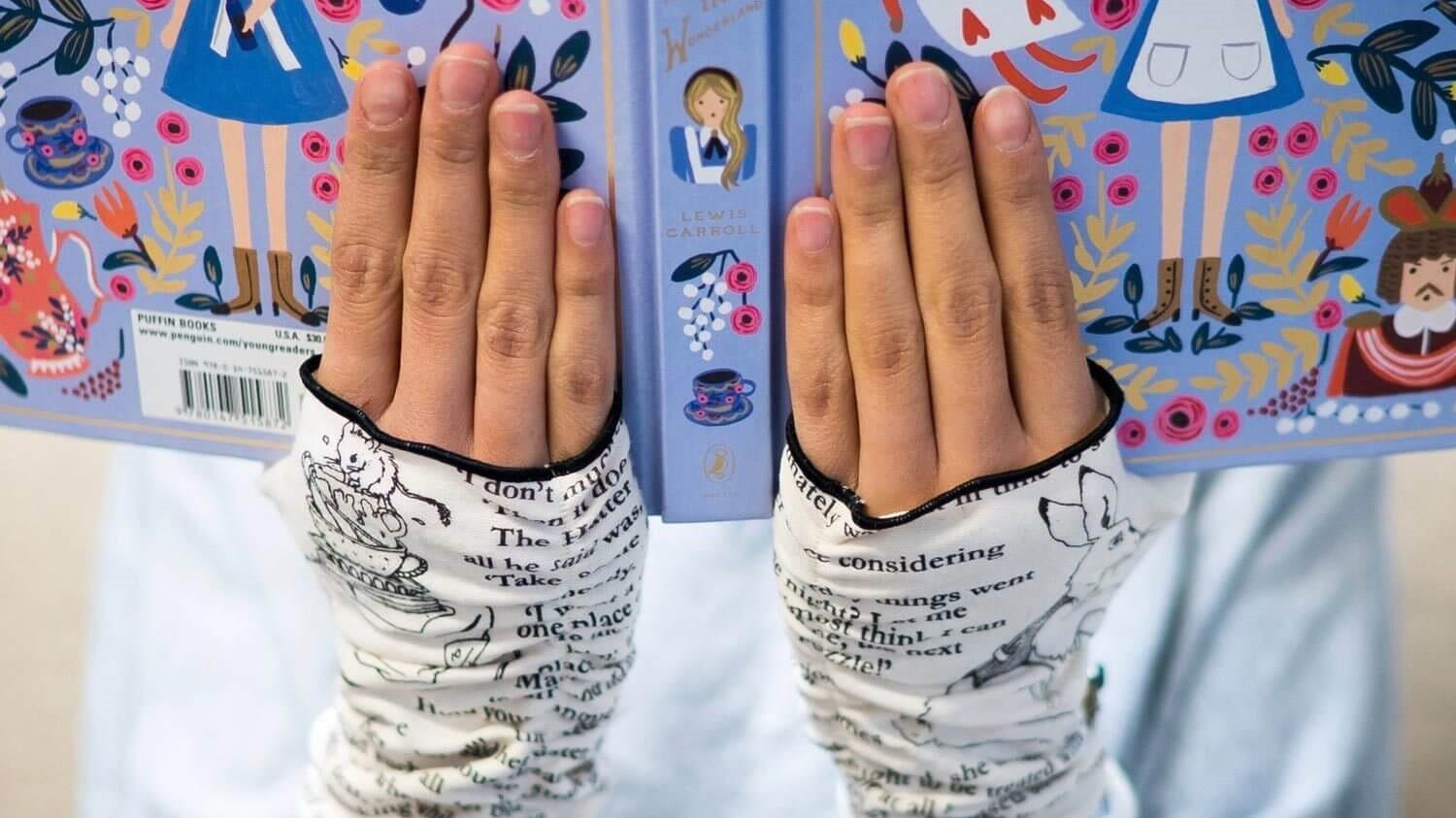 Someone wearing the 'Alice in Wonderland' fingerless gloves and holding a copy of the book.