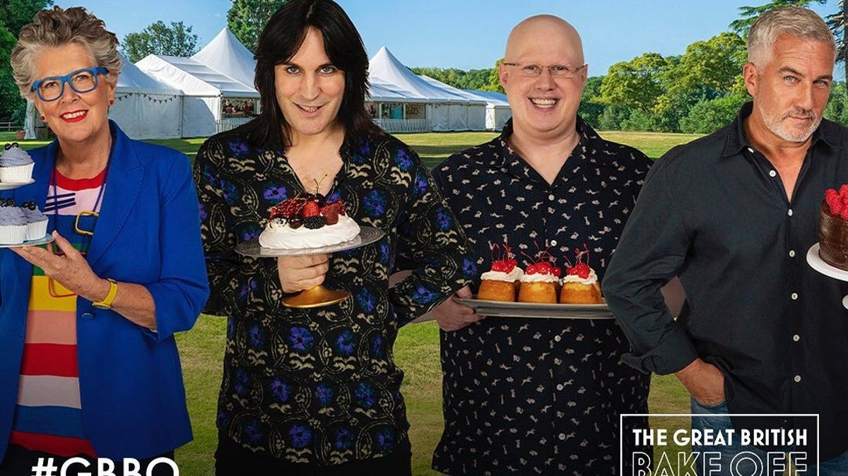 """The judges from """"The Great British Bake-Off"""" holding baked goods."""