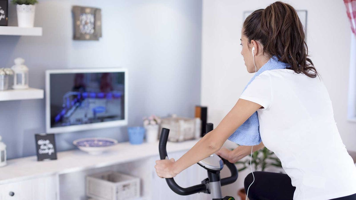 A woman working out using an exercise bike in her living room.