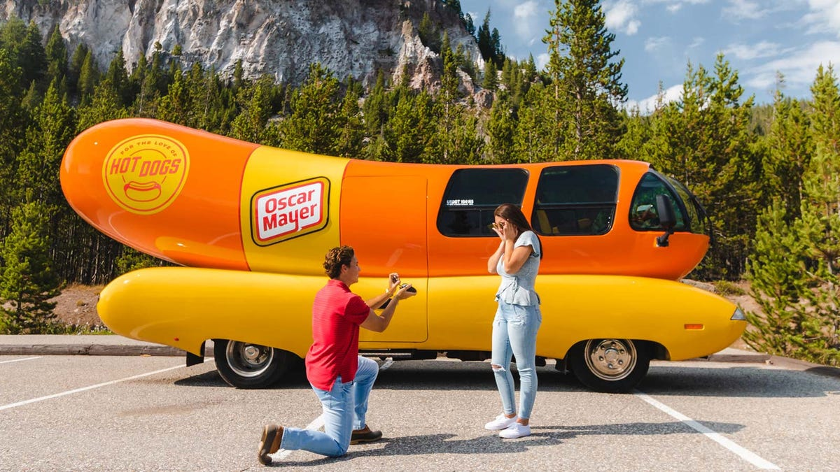 A man proposing in front of the Oscar Mayer wiener mobile in Yosemite National Park.