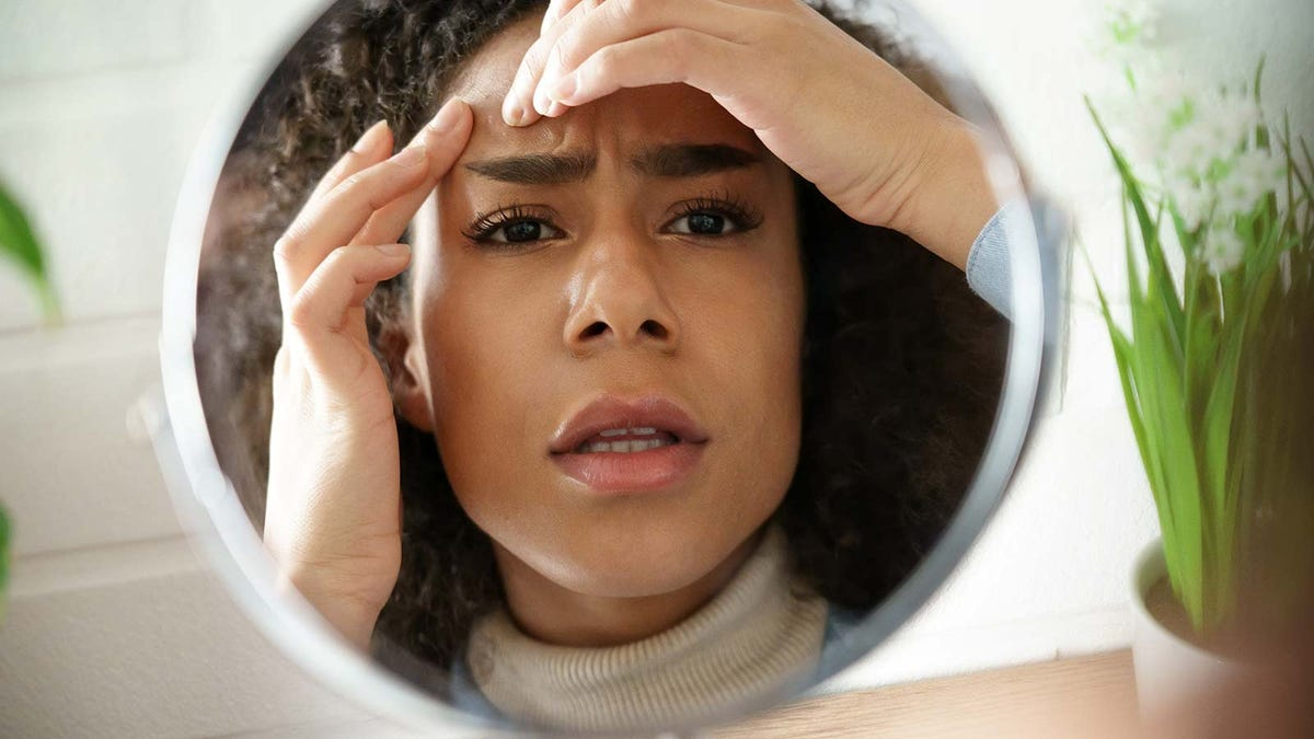 A woman looking at her skin with concern in a large makeup mirror.
