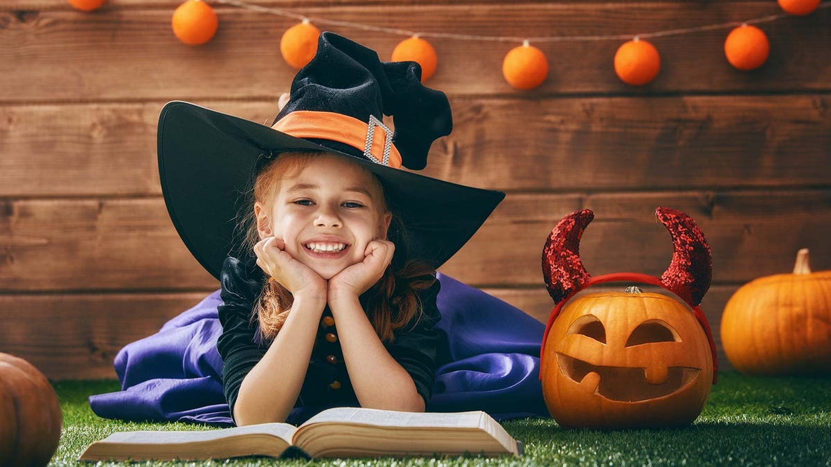 A young girl wearing a witch costume, reading a book next to pumpkins and other fall decorations.