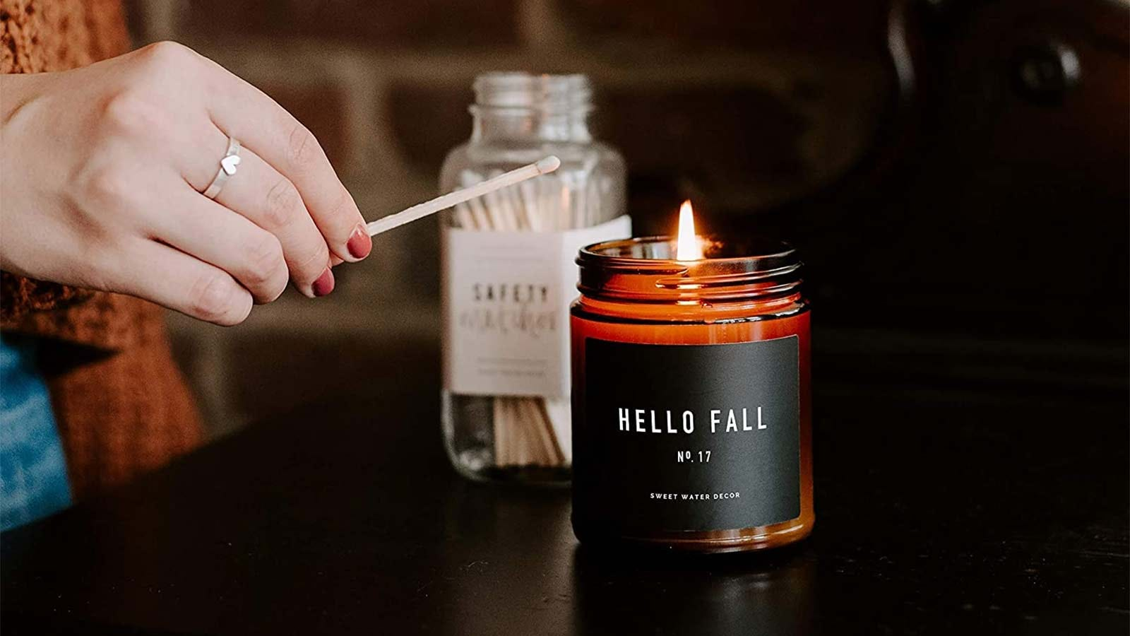 A woman's hand lighting a Sweet Water Decor Hello Fall candle.