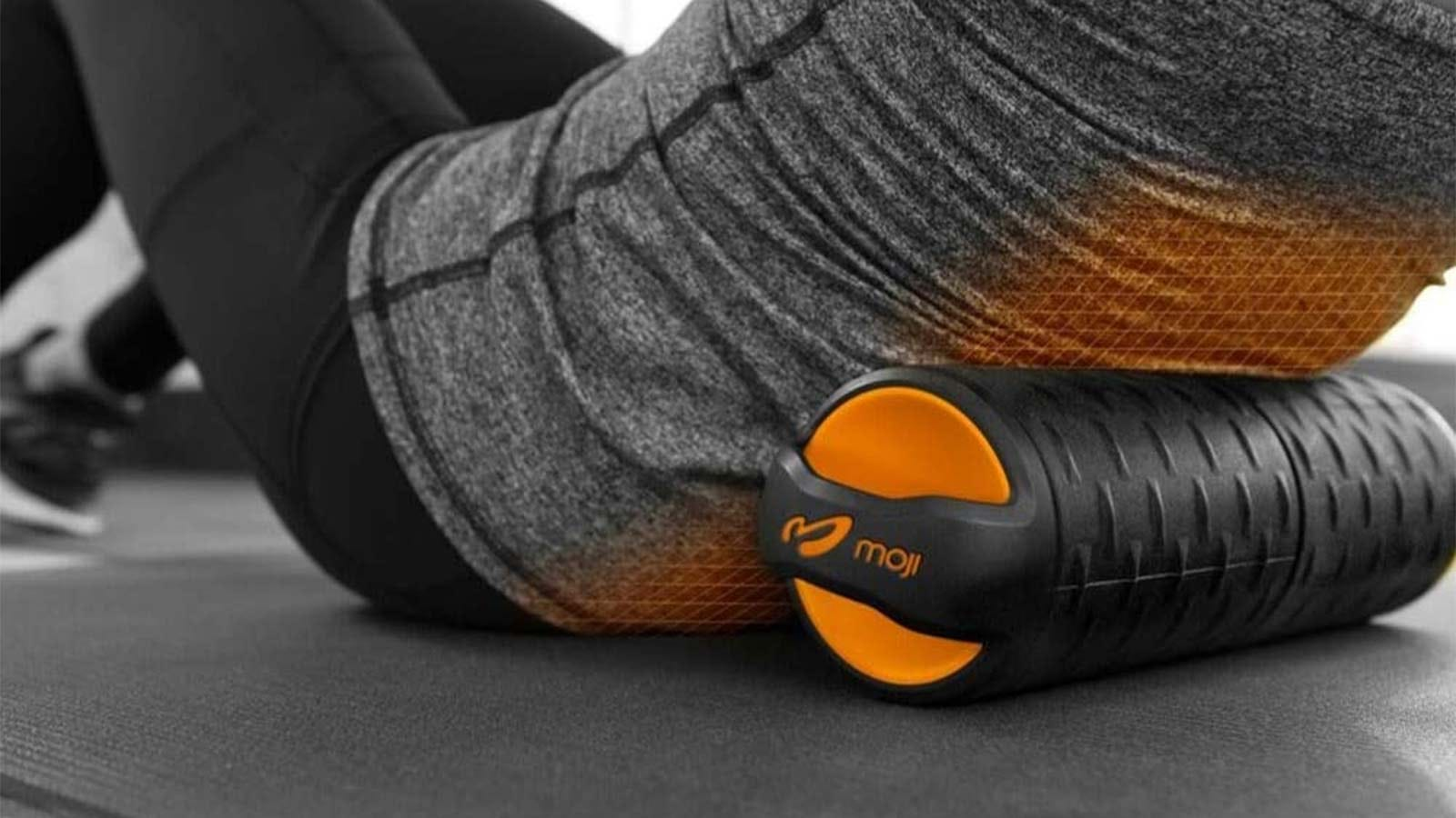 Someone using the Moji heated foam roller on their mid-back to help roll out tension.