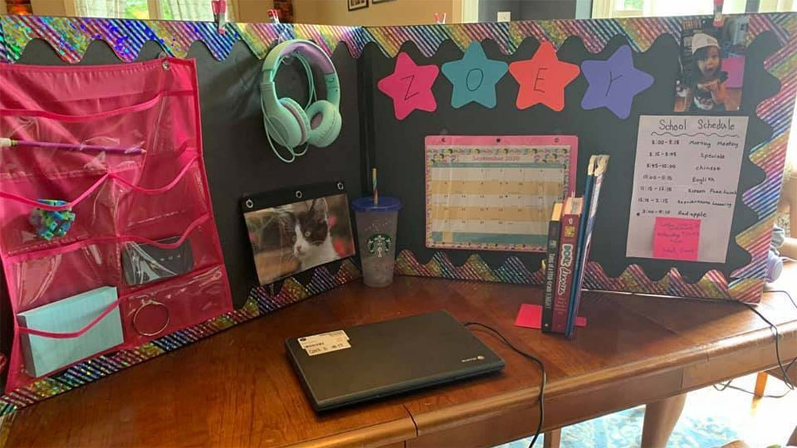 A center-fold style poster board set up as a cubicle for a young girl to use while remote learning.