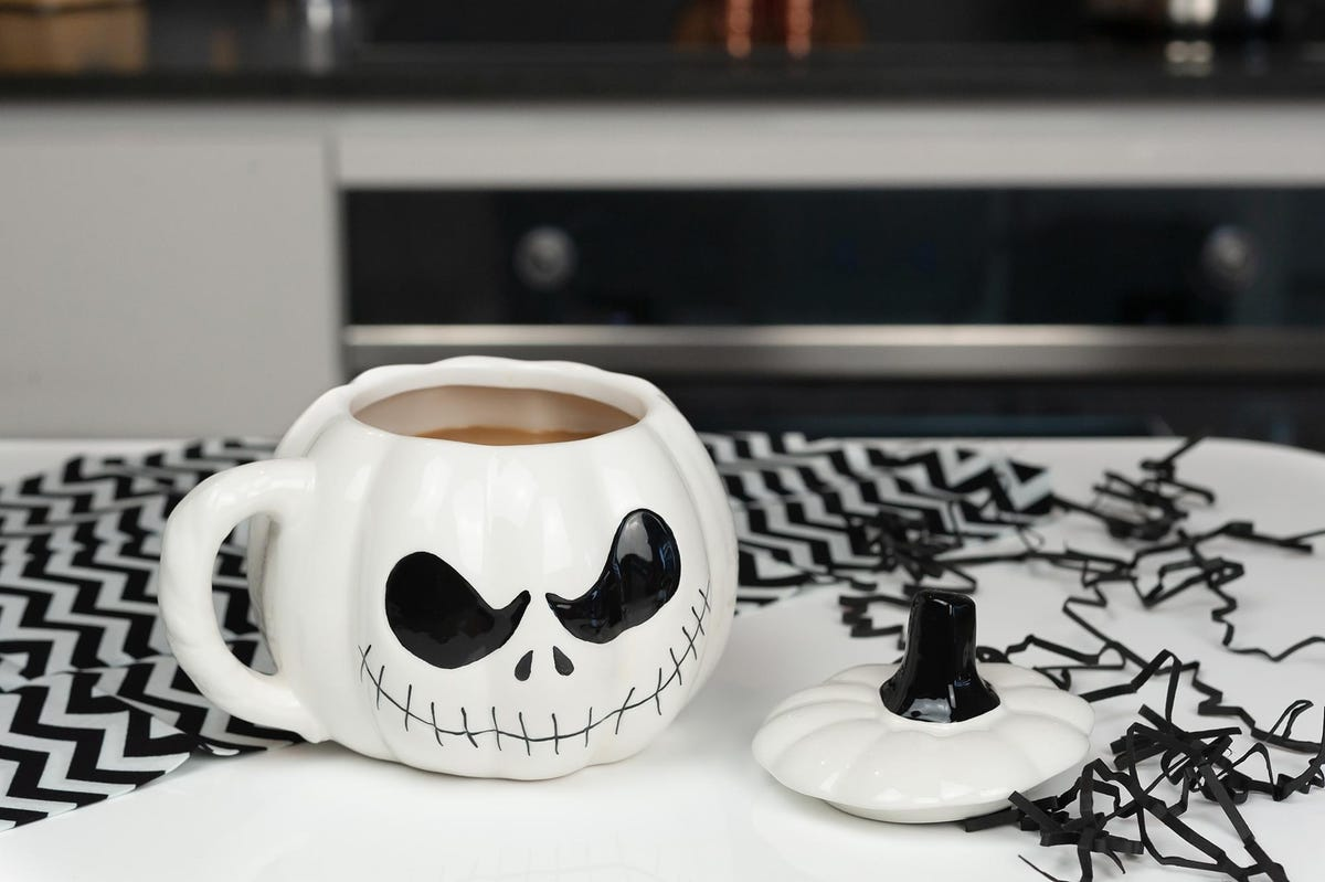"""A """"The Nightmare Before Christmas"""" Pumpkin King mug with it's lid sitting next to it on a kitchen counter."""