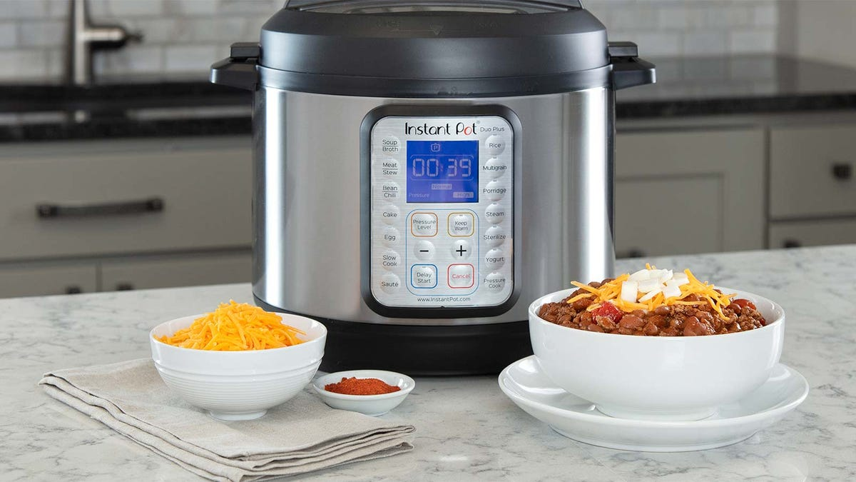 An Instant Pot on a counter next to some bowls of chili, cheese, and salsa.